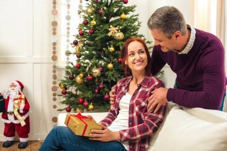Foto de Hombre que presenta el regalo de Navidad para mujer joven feliz en casa - Imagen libre de derechos
