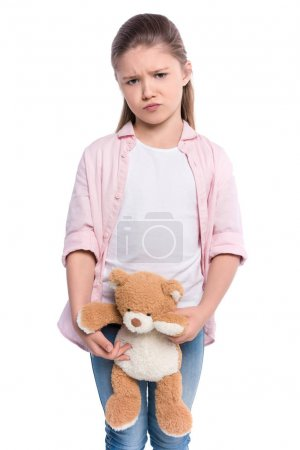 Grumpy girl holding teddy bear
