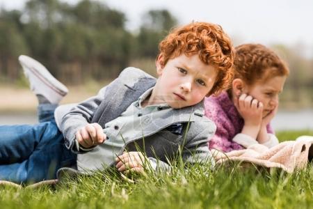 Siblings lying on grass