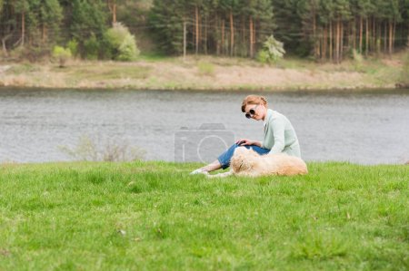 Woman with dog on grass