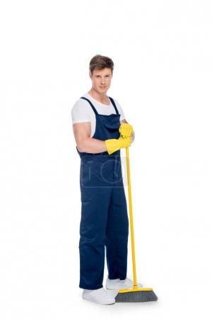 cleaner in rubber gloves with broom