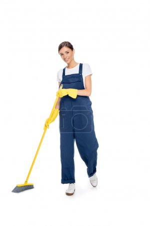 Photo for Smiling cleaner in uniform with broom in hands looking at camera isolated on white - Royalty Free Image