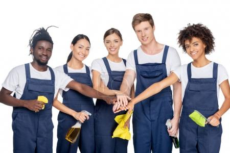 Photo for Group of young multiethnic cleaners with various cleaning supplies holding hands together isolated on white - Royalty Free Image