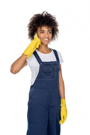 african american cleaner with smartphone