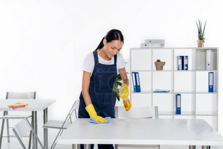young cleaner wiping table