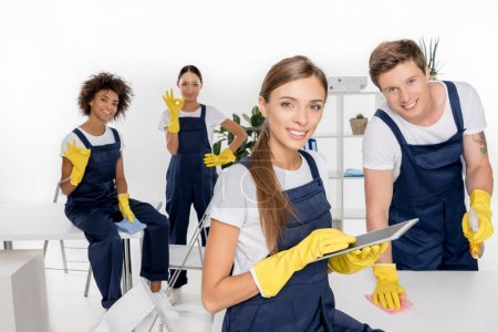 Photo for Smiling young female cleaner using digital tablet while colleagues working behind - Royalty Free Image