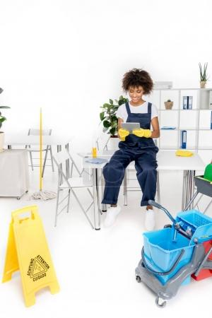 african american cleaner with digital tablet