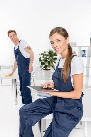 Young cleaners with digital tablet and rag
