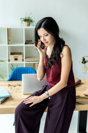 Photo for Young businesswoman talking on smartphone while sitting on table in office - Royalty Free Image