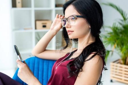 businesswoman in earphones with smartphone