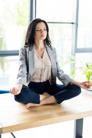 businesswoman meditating at workplace