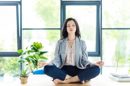 Photo for Relaxed businesswoman with eyes closed meditating at workplace in office - Royalty Free Image