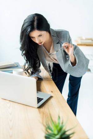Photo pour Portrait de femme d'affaires ciblée travaillant sur ordinateur portable au lieu de travail au bureau - image libre de droit