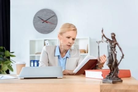 Photo for Mature female lawyer sitting at workplace and reading book - Royalty Free Image