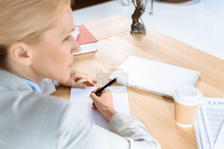 businesswoman writing documents with pen