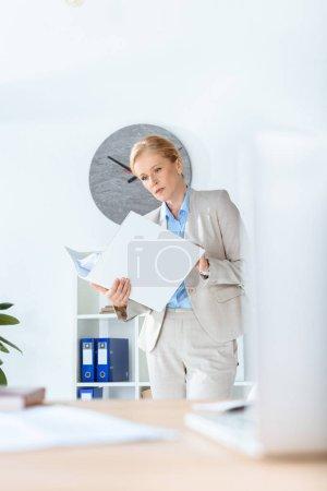 Foto de Empresaria madura con carpeta de documentos en la oficina moderna - Imagen libre de derechos