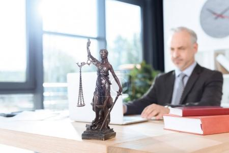 Photo for Themis sculpture on table and lawyer working with laptop on background - Royalty Free Image