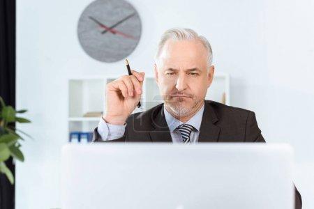 Foto de Empresario maduro pensativo con la pluma en laptop - Imagen libre de derechos