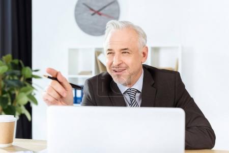 Foto de Empresario maduro sentado con el ordenador portátil y apuntando a algún lugar - Imagen libre de derechos