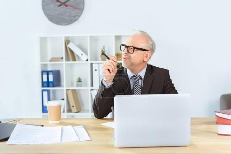 Foto de Wotking empresario pensativo con la laptop en la oficina moderna - Imagen libre de derechos