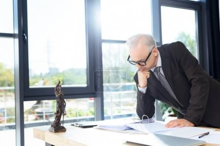 Photo for Mature thoughtful lawyer looking at documents in modern office - Royalty Free Image