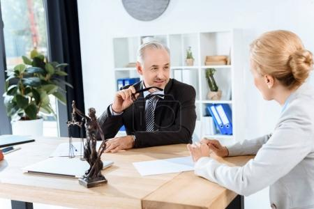 Photo for Mature lawyers discussing documents in office - Royalty Free Image