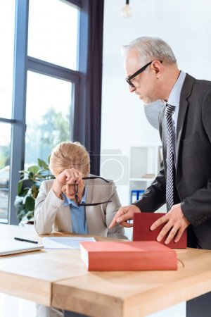 businessman talking to overworked colleague