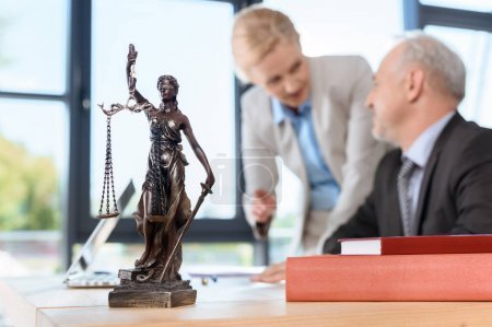 Photo for Smiling mature lawyers discussing plans at workplace - Royalty Free Image