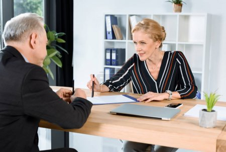businesswoman giving contract to partner