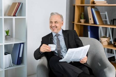 Foto de Riendo el maduro empresario en sillón bebiendo café en la oficina - Imagen libre de derechos