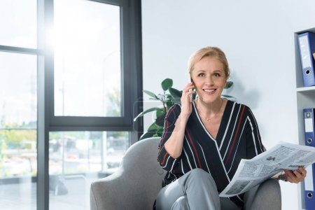 businesswoman with newspaper talking by phone