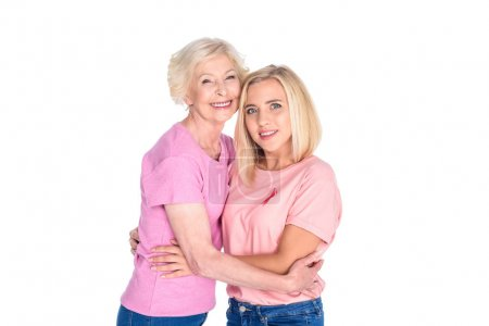 Photo for Cheerful caucasian women in pink t-shirts hugging and smiling at camera isolated on white - Royalty Free Image