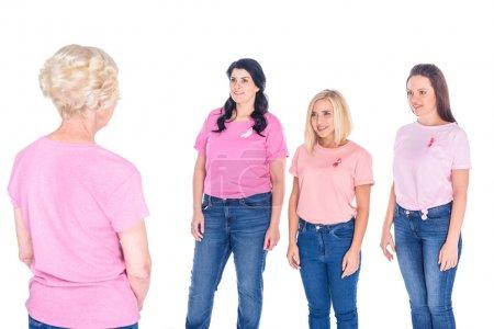 Photo pour Jeunes femmes souriantes en t-shirts roses avec des rubans regardant femme âgée isolée sur blanc - image libre de droit