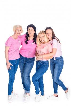 Photo pour Gaies femmes en t-shirts roses avec des rubans souriant à la caméra isolée sur blanc - image libre de droit