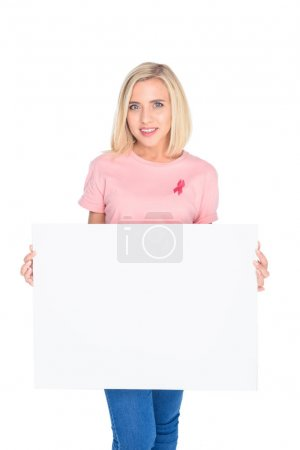 Photo for Cheerful young woman in pink t-shirt with ribbon holding blank banner and smiling at camera - Royalty Free Image