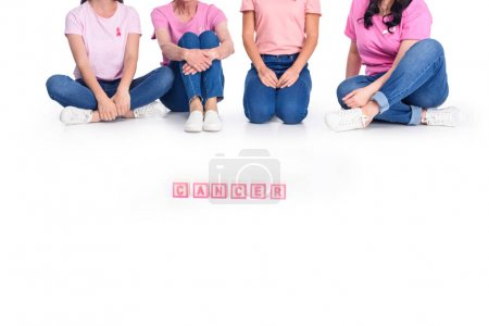 women in pink t-shirts with cancer inscription