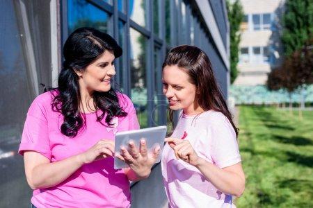 Photo pour Des jeunes femmes souriantes en t-shirts roses utilisant ensemble une tablette numérique - image libre de droit