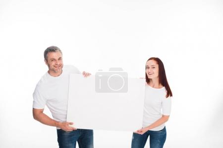 Photo for Smiling young couple holding empty card, isolated on white - Royalty Free Image
