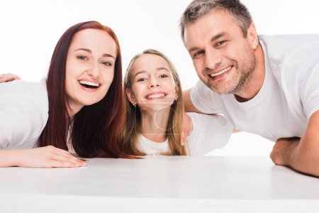 Photo for Young smiling family hugging and looking at camera, isolated on white - Royalty Free Image