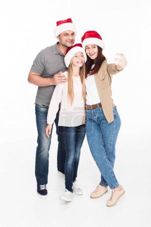 family in santa hats taking selfie