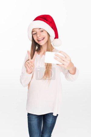 Photo pour Adorable adolescent en bonnet de noel avec le symbole de la paix en tenant selfie sur smartphone, isolé sur blanc - image libre de droit