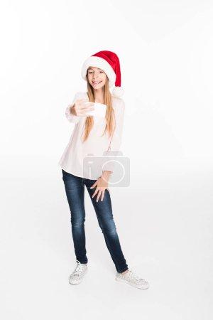 child in santa hat taking selfie