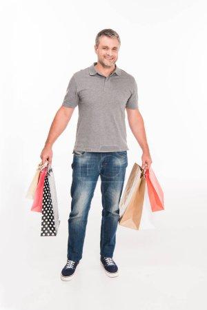 Photo pour Sourire d'homme portant des sacs à provisions, isolé sur blanc - image libre de droit