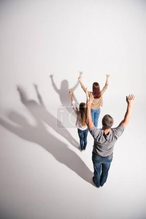 Photo for Young family standing with raised arms with shadows on white - Royalty Free Image