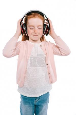 Photo pour Enfant féminin souriant aux yeux fermés écoutant de la musique avec écouteurs, isolé sur blanc - image libre de droit