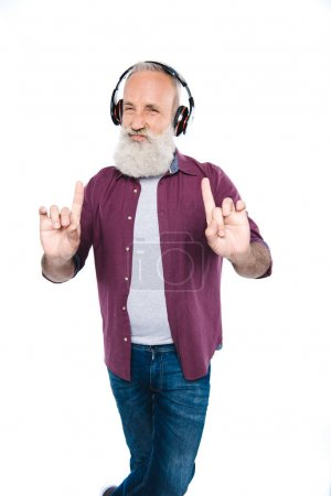 senior man listening music with headphones