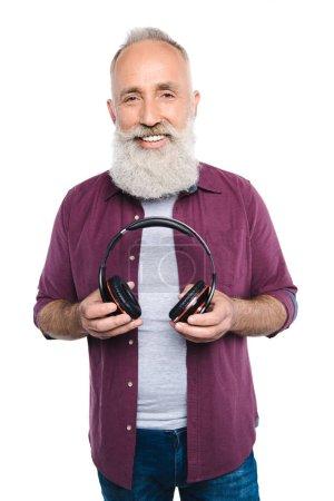 Photo pour Homme barbu âgé joyeux tenant écouteurs, isolé sur blanc - image libre de droit