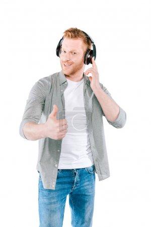 Photo pour Bel homme souriant avec pouce levé écoutant de la musique avec écouteurs, isolé sur blanc - image libre de droit