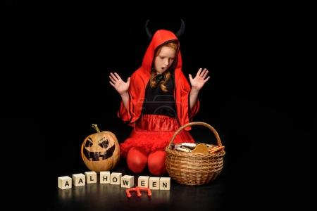 Shocked child in costume of devil