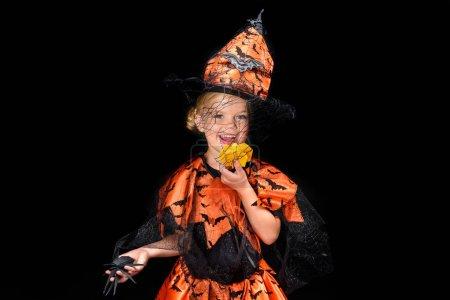 little witch eating pumpkin